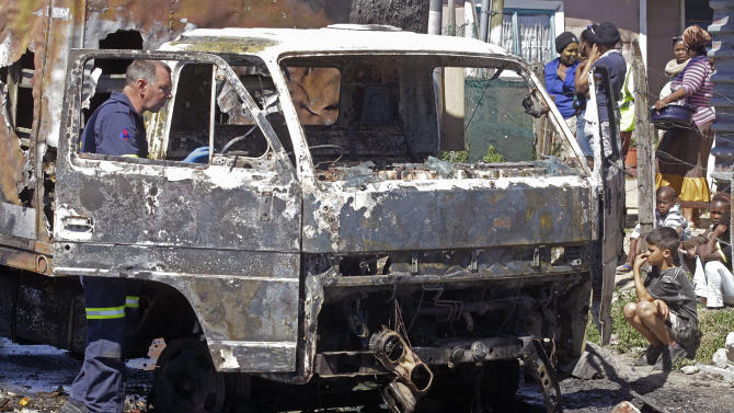 A South African Police forensic team member, left, looks for leads in a burnt out truck near  Cape Town, South Africa, Thursday, Oct 11, 2012. South African truck drivers are on strike over wages for the past three week's with around twenty five trucks being burnt around Cape Town city resulting in the death of two drivers  after there trucks were set alight. (AP Photo/Schalk van Zuydam)