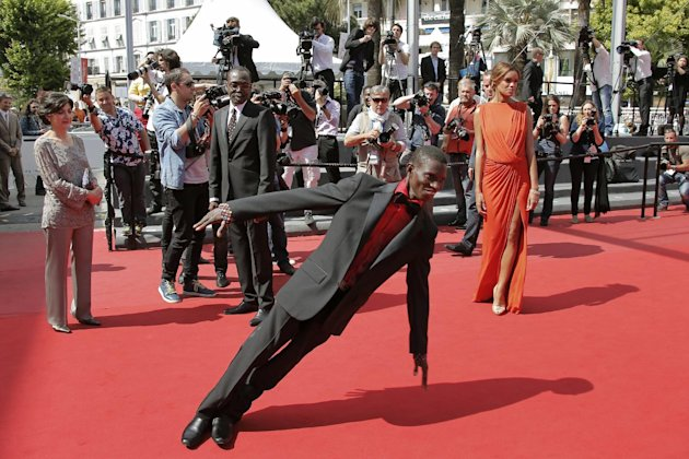 Actor Souleymane Deme, foreground, performs a dance as producer Florence Stern, left, director Mahamat-Saleh Haroun, rear centre, and actress Anais Monory, right, watch him as they arrive for the scre