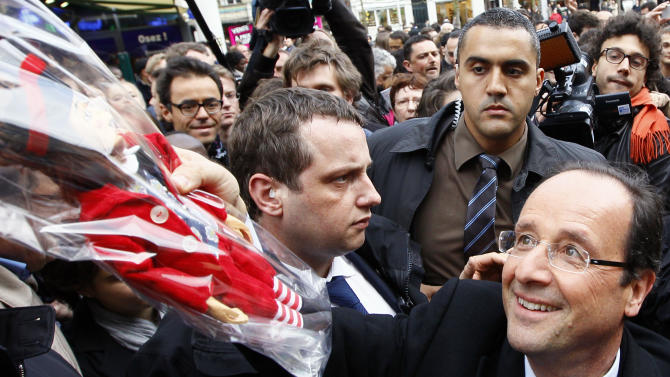 """French Socialist Party candidate for the 2012 presidential elections Francois Hollande, right, receives a traditional local puppet representing a """"Comedy Valet with Big Heart"""" called """"La Fleur"""" as a gift during a campaign meeting in Amiens, northern France, Wednesday, April 18, 2012. The first round of the election will take place on April 22, followed by a second round on May 6, 2012. (AP Photo/Francois Mori)"""