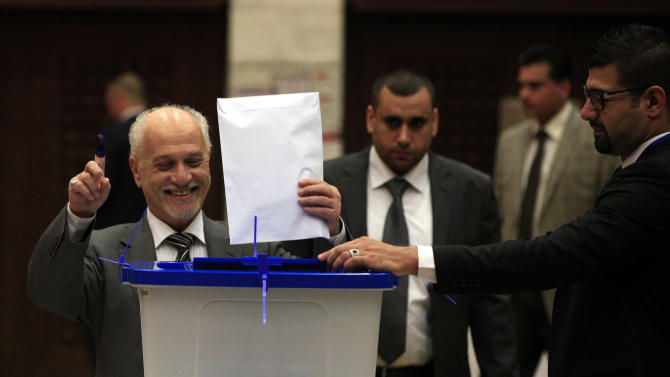 Iraqi Deputy Prime Minister Hussain al-Shahristani holds up an ink-marked finger after casting his ballot in the country's provincial elections at a polling center in the heavily fortified Green Zone in Baghdad, Iraq, Saturday, April 20, 2013. Polls opened amid tight security in Iraq on Saturday for regional elections in the country's first vote since the U.S. military withdrawal, marking an important test of the country's stability. (AP Photo/ Karim Kadim)