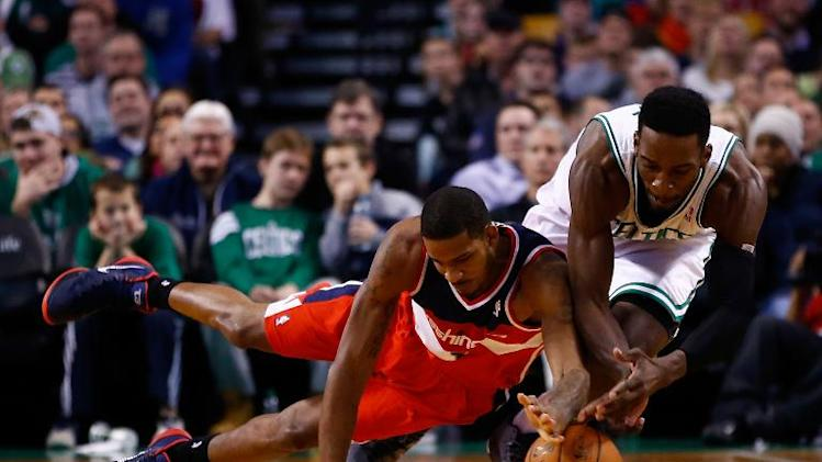 Jeff Green (R) of the Boston Celtics and Trevor Ariza of the Washington Wizards scramble for a loose ball in the second half during the game at TD Garden on December 21, 2013 in Boston, Massachusetts