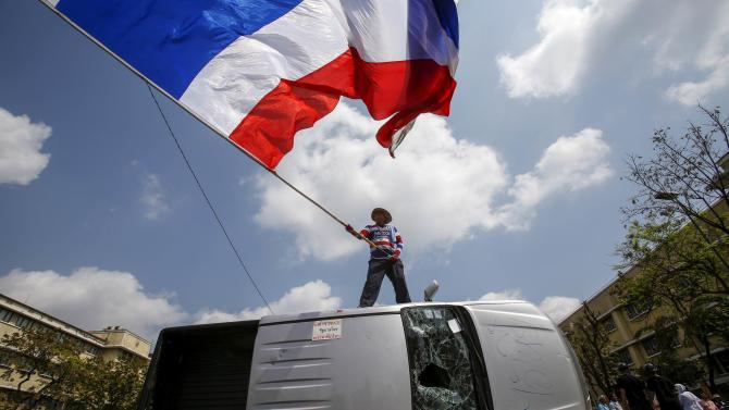 An anti-government protester stands on a damaged police vehicle as he waves a Thai national flag after clashes with riot police officers in Bangkok