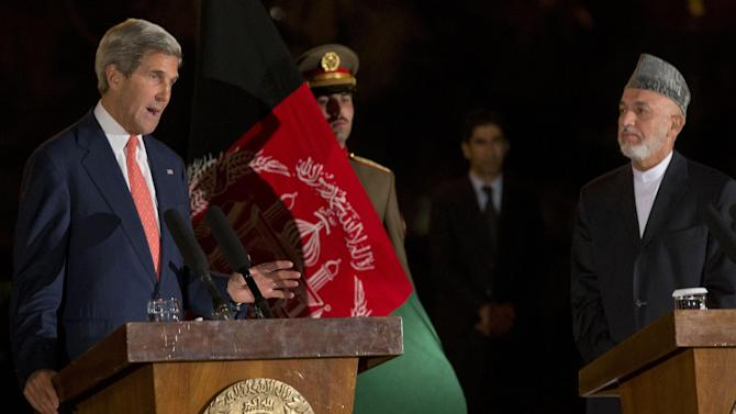 In this Saturday, Oct. 12, 2013 photo, U.S. Secretary of State John Kerry, left, gestures as he speaks during a news conference with Afghan President Hamid Karzai, right, at the Presidential Palace during an unannounced stop in Kabul, Afghanistan, as a deadline approaches for a security deal about the future of U.S. troops in the country. Kerry and Karzai announced a partial agreement was reached on a security accord, but the potentially deal-breaking issue of jurisdiction for American forces remains unresolved. (AP Photo/Jacquelyn Martin, Pool)