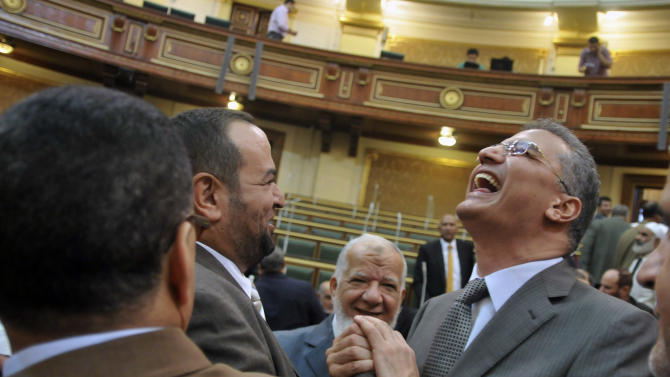 Egyptian lawmakers greet each other at a brief session of Parliament, the first since the country's high court ruled the chamber unconstitutional, in Cairo, Egypt, Tuesday, July 10, 2012. Egypt's Islamist-dominated parliament convened Tuesday in defiance of a ruling by the country's highest court and swiftly voted to seek a legal opinion on the decision that invalidated the chamber over apparent election irregularities. (AP Photo/Mohammed Asad)