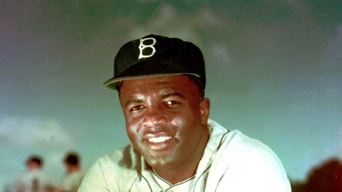 "FILE - Brooklyn Dodgers baseball player Jackie Robinson poses in 1952. Kansas City's Negro Leagues Baseball Museum is hosting an advance screening of an upcoming movie about Robinson, who broke major league baseball's color barrier. Thomas Butch of the financial firm Waddell and Reed announced Wednesday, March 20, 2013 that actors Harrison Ford and Andre Holland will be among those appearing at an April 11 screening of ""42.""   (AP Photo/File)"