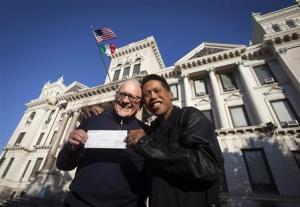 Rich Kiamco and David Gibson pose for a portrait with their receipt for their wedding license in Jersey City