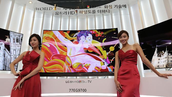 Models pose with LG Electronics' 77-inch Ultra organic light-emitting diode (OLED) TV during a press unveiling in Seoul, South Korea, Monday, Aug. 25, 2014. LG Electronics Inc. is sticking with its strategy of using the exceptionally expensive OLED display technology for TVs, announcing two new giant models with ultra-high definition screens. (AP Photo/Ahn Young-joon)