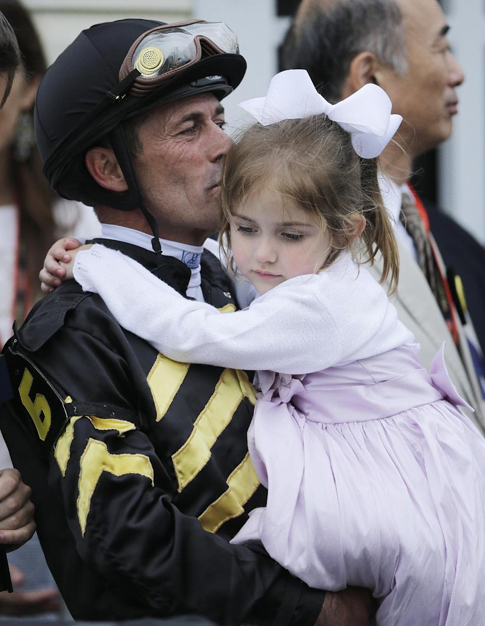 Jockey Gary Stevens kisses his daughter Maddie Stevens in the winner's circle after riding Oxbow to win the 138th Preakness Stakes horse race at Pimlico Race Course, Saturday, May 18, 2013, in Baltimore. (AP Photo/Matt Slocum)
