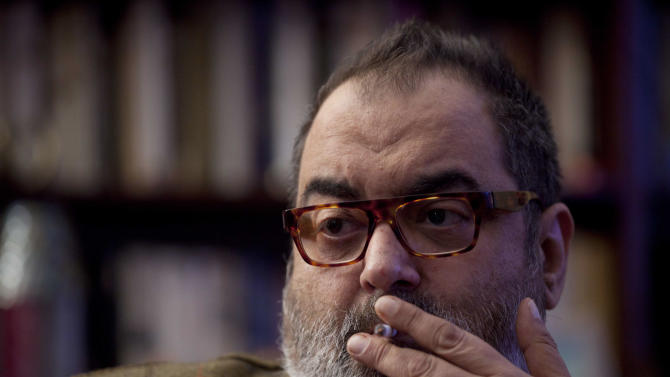 In this photo taken June 7, 2012, journalist Jorge Lanata smokes during an interview in Buenos Aires, Argentina. Argentines have many news outlets to choose from, and nearly all media have taken strong positions for or against the government, and frequently spend ink and airtime accusing the other side of bias. Lanata, a leading Argentine journalist has challenged Argentina's President Cristina Fernandez. (AP Photo/Natacha Pisarenko)