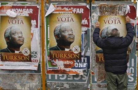 A man tries to remove a spoof poster supporting Ghana's Cardinal Peter Turkson from a billboard in Rome, March 1, 2013. REUTERS/Alessandro Bianchi