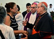 Cuban Cardinal Jaime Ortega (R) greets Ofelia Acevedo (L), the widow of Cuban dissident Oswaldo Paya, on July 24, during his funeral in Havana. Acevedo rejected a government report that blamed the car crash that killed her husband and a fellow dissident on the vehicle&#39;s driver