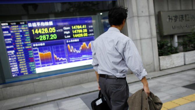 A man walks outside a securities firm in Tokyo Wednesday, Oct. 23, 2013 as Japan's Nikkei 225 lost 287.20 points, or 1.7 percent, and closed at 14,457.52. Asian stock markets mostly fell Wednesday, hit by slower U.S. hiring and reports of tighter money market conditions in China that could check its economic recovery. (AP Photo/Junji Kurokawa)