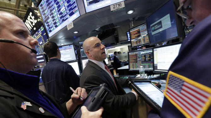 Specialist Henry Becker, center, works at his post on the floor of the New York Stock Exchange Tuesday, Feb. 5, 2013. Stocks are turning higher in early trading on Wall Street following a spike in home prices and strong earnings reports from Kellogg and other U.S. companies. (AP Photo/Richard Drew)