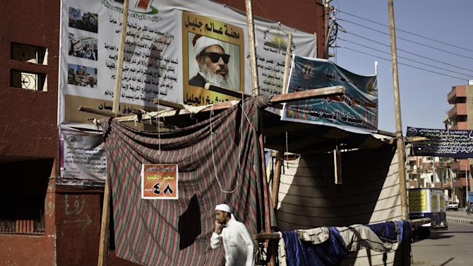 "In this Sunday, March 17, 2013 photo, an Egyptian man walks past banners hung up by members of Gamaa Islamiya in front of el-Gamaayah el-Sharaayah mosque also used as Gamaa's headquarters, not pictured, in Assiut, southern Egypt. The Gamaa says its move is in response to a strike last week by some of the police in Assiut. The group unilaterally declared it would set up ""popular committees"" to carry out security duties in the police's absence. Riding on motorbikes and waving banners, hundreds of Gamaa supporters toured the city last week to assure residents that the group was capable of maintaining law and order if the strike continues or spreads. The banner, top center, shows Egyptian spiritual leader Sheikh Omar Abdel-Rahman, who is currently imprisoned in the US. (AP Photo/Nariman El-Mofty)"