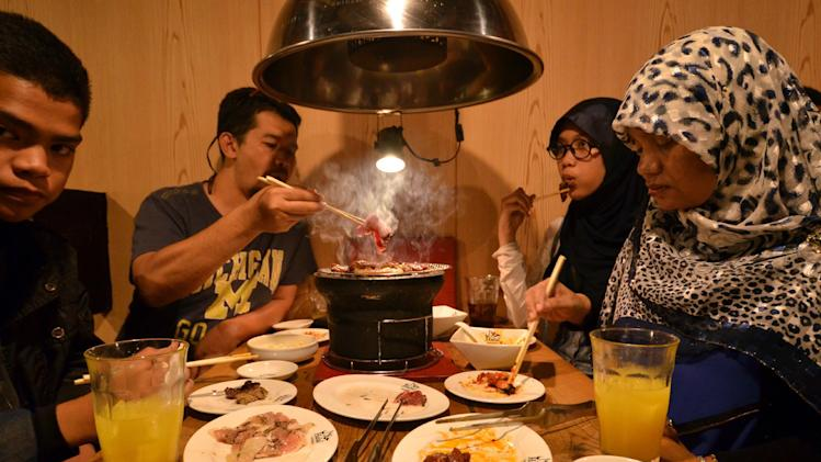Thai Muslim tourists enjoying Halal certified foods at a barbecue restaurant in Tokyo.