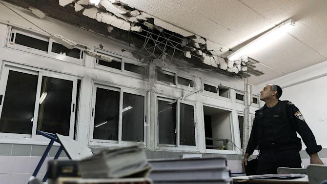 An Israeli policeman examines the damage to a school classroom hit by a rocket fired by Palestinian militants from the Gaza Strip, at the southern Israeli city of Ashkelon, Monday, Nov. 19, 2012.  Israeli aircraft struck crowded areas in the Gaza Strip and killed a senior militant with a missile strike on a media center Monday, driving up the Palestinian death toll to 96, as Israel broadened its targets in the 6-day-old offensive meant to quell Hamas rocket fire on Israel. (AP Photo/Tsafrir Abayov)