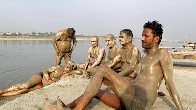 Men relax after applying mud on their bodies to cool themselves off on a hot summer morning on the banks of the river Ganges in Allahabad
