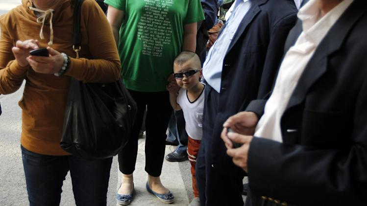 A child wearing sunglasses peeks through a group of onlookers and journalists gathered outside a hospital where blind Chinese activist Chen Guangcheng is believed to be seeking treatment in Beijing, China, Wednesday, May 2, 2012.  Chen who sparked a diplomatic tussle by holing up in the U.S. Embassy in Beijing for six days emerged Wednesday after U.S. officials said China had assured his safety. (AP Photo/Ng Han Guan)