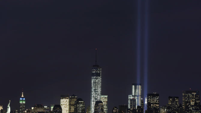 The Tribute in Light rises above the lower Manhattan skyline and One World Trade Center, center, in a test of the memorial light display, Monday, Sept. 9, 2013 in New York. The twin beams of light will also appear Wednesday, Sept. 11, twelve years after the terrorist attacks of Sept. 11, 2001. The Statue of Liberty and Empire State Building are at far left. (AP Photo/Mark Lennihan)