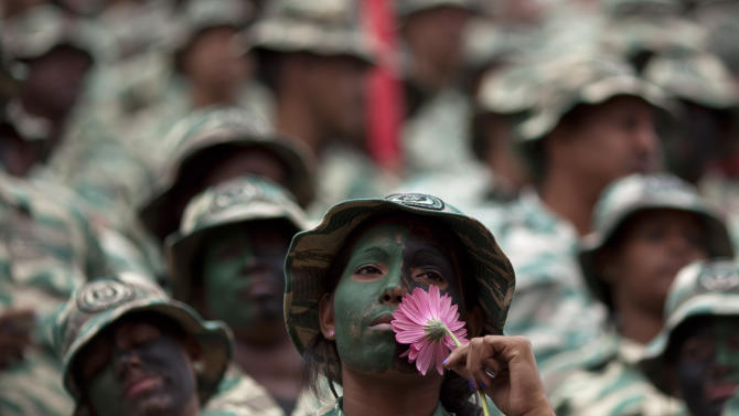 A female member of Venezuela's Bolivarian militia, in uniform with her face painted, holds a flower during a rally in Caracas, Venezuela, Thursday, Jan. 10, 2013. Supporters of Venezuelan President Hugo Chavez rallied outside his presidential palace Thursday in an exuberant symbolic inauguration for a leader too ill to return home for the real thing. With Chavez out of sight in a Cuban hospital fighting a severe respiratory infection more than a month after cancer surgery, his swearing-in ceremony has been indefinitely postponed, despite opposition complaints. (AP Photo/Ariana Cubillos)