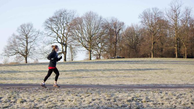 A woman runs through a frost covered field in Hampstead Heath in north London