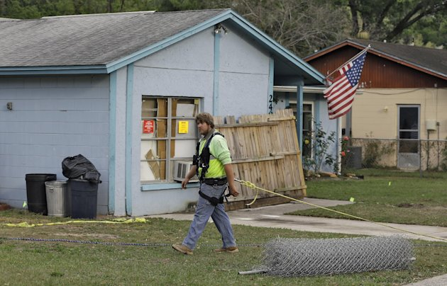 An engineer, tethered with a safety line, walks in front of a home where a sinkhole opened up underneath a bedroom late Thursday evening and swallowed a man in Seffner, Fla. on Saturday, March 2, 2013