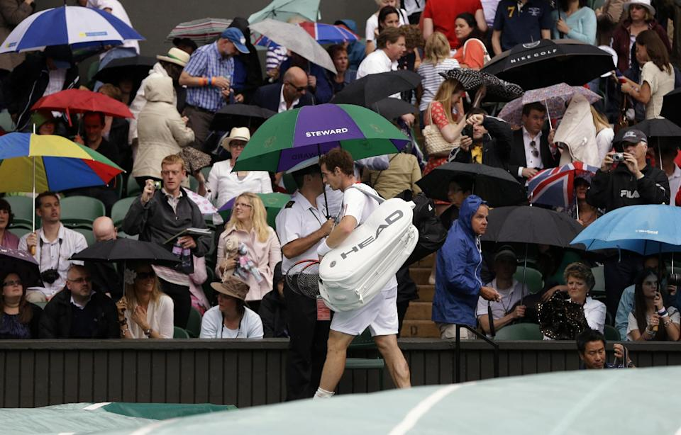 Andy Murray of Britain walks off the court as rain delays play during the men's final match against Roger Federer of Switzerland at the All England Lawn Tennis Championships at Wimbledon, England, Sunday, July 8, 2012. (AP Photo/Kirsty Wigglesworth)