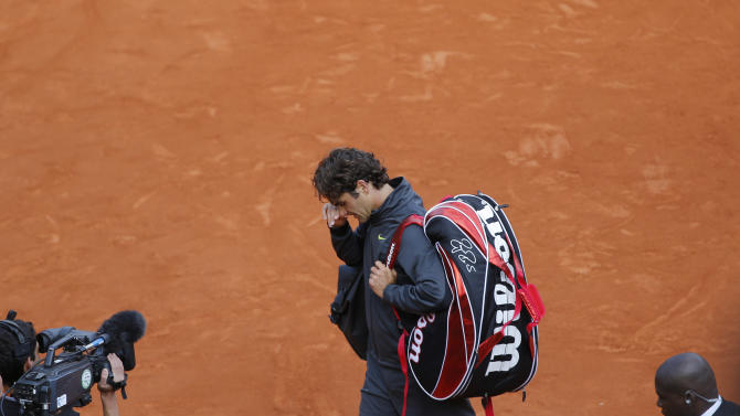 Roger Federer of Switzerland leaves center court after losing his semi final match against Novak Djokovic of Serbai at the French Open tennis tournament in Roland Garros stadium in Paris, Friday June 8, 2012. Djokovic won in three sets 6-4, 7-5, 6-3. (AP Photo/Christophe Ena)
