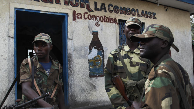 M23 rebels  stand outside a bar in the eastern Congo town of Sake, some 27 kms west of Goma, Thursday Nov. 29, 2012. Rebels, who last week seized one of the most important cities in eastern Congo and advanced beyond, said Thursday that they had pulled back several miles (kilometers ) to the town of Sake and were on track to leave the key city of Goma by Friday, in accordance with a deadline imposed by the international community.(AP Photo/Jerome Delay)