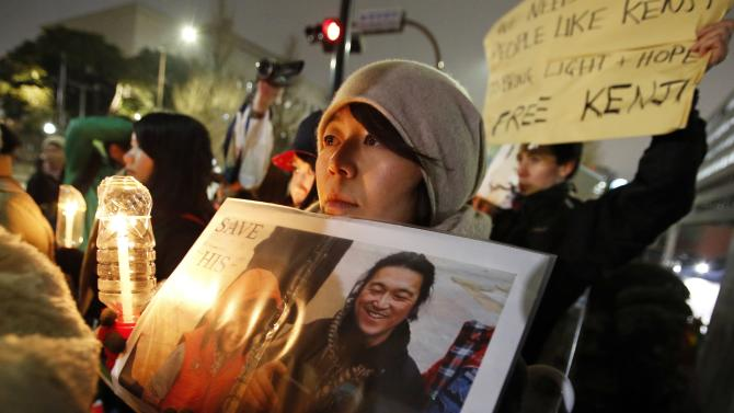 People holding placards take part in a vigil in front of Prime Minister Shinzo Abe's official residence in Tokyo,