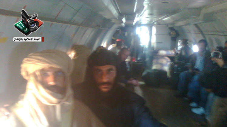 In this image provided by the Zintan Media Center, Seif al-Islam Gadhafi, left, is guarded by a Libyan fighter as he is transported to Zintan, Libya, by a transport aircraft following his capture near the Niger border early Saturday Nov 19 2011. Moammar Gadhafi's son, the only wanted member of the ousted ruling family to remain at large _ was captured as he traveled with aides in a convoy in Libya's southern desert. (AP Photo / Zintan Media Center,HO) EDITORIAL USE ONLY LOGO MUST BE USED MANDATORY CREDIT