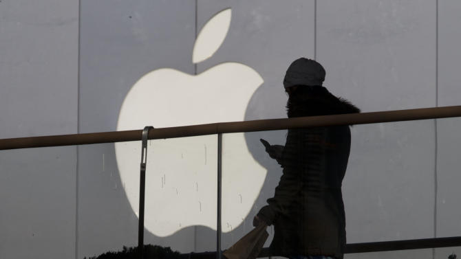 FILE - In this Dec. 23, 2013 file photo, a woman using a phone walks past Apple's logo near its retail outlet in Beijing. Apple reports quarterly earnings on Wednesday, April 23, 2014. (AP Photo/Ng Han Guan, File)