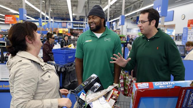 """IMAGE DISTRIBUTED FOR SUBWAY - New England linebacker Jerod Mayo, center, and Jared """"The SUBWAY Guy"""", right, surprise unsuspecting customer Janet Cugini of Boston, left, by footing her bill at Wal-Mart as part of SUBWAY Customer Appreciation Month on Tuesday,  Dec. 11, 2012, in Boston.. (Photo by Bizuayehu Tesfaye/Invision for SUBWAY/AP Images)"""