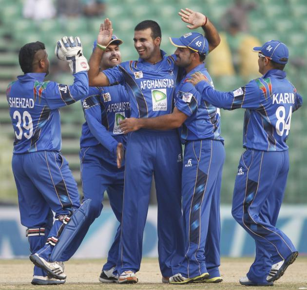 Afghanistan's fielders congratulate bowler Zadran as he dismissed Pakistan's Afridi successfully during their Asia Cup 2014 ODI cricket match in Fatullah