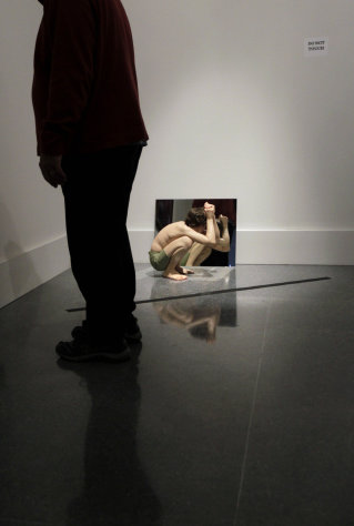 "In this Wednesday, Nov. 14, 2012 photo, a patron, foreground, stands in front of the installation ""Crouching Boy In Mirror,"" by artist Ron Mueck, at the New Orleans Museum of Art, in New Orleans. The piece is part of ""Lifelike,"" a traveling exhibit at the New Orleans Museum of Art through Jan. 27. (AP Photo/Gerald Herbert)"