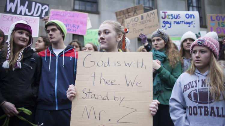An Eastside Catholic High School student holds up a sign during a rally in support of the school's former Vice Principal Mark Zmuda at the Archdiocese of Seattle chancery building in Seattle, Washington