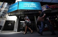 Pedestrians walk past a sign welcoming Facebook at the NASDAQ stock exchange on Times Square in New York, on May 18. Nasdaq raised to $62 million the amount of money it will set aside to cover trading losses due to computer glitches that disrupted the launch of Facebook shares onto the market