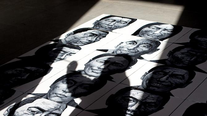 In this Dec. 25, 2012 photo, Beijing-based artist Liu Yi casts his shadow on his painting of portraits of Tibetans who have self-immolated over the past three years as he works at his studio in Songzhuang art village in Tongzhou, on the outskirt of Beijing. Chinese authorities are responding to an intensified wave of Tibetan self-immolation protests against Chinese rule by clamping down even harder — criminalizing the suicides, arresting protesters' friends and even confiscating thousands of satellite TV dishes. (AP Photo/Andy Wong)