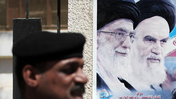 In this Sept. 12, 2012, photo, an Iraqi soldier stands guard next to a poster depicting late Iran's spiritual leaders Ayatollah Khomeini, right, and Ayatollah Khamenei, left, in Basra, 340 miles (547 kilometers) southeast of Baghdad, Iraq. After years of growing influence, a new sign of Iran's presence in Iraq has hit the streets. Thousands of signs, that is, depicting Iran's supreme leader gently smiling to a population once mobilized against the Islamic Republic in eight years of war. (AP Photo/Nabil al-Jurani)