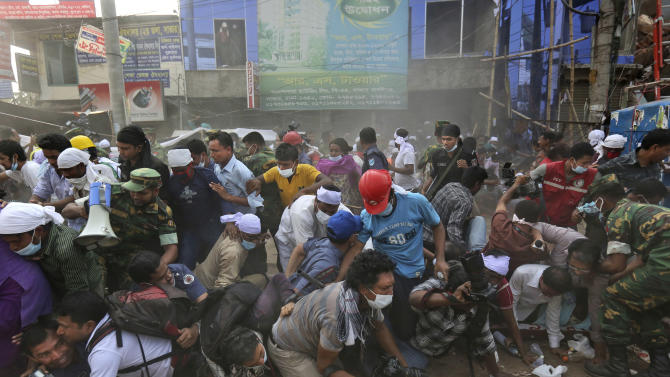 Bangladeshi rescue workers and media fall on top of each other in a stampede after the crowd panic when someone shouted a section of building might collapse, at the site of a building that collapsed Wednesday in Savar, near Dhaka, Bangladesh, Friday, April 26, 2013. The death toll reached hundreds of people as rescuers continued to search for injured and missing, after a huge section of an eight-story building that housed several garment factories splintered into a pile of concrete.(AP Photo/Kevin Frayer)