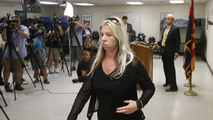 Jeanne Brown, who had a father and sister murdered, leaves the room after speaking at a news conference after the nearly two hour long execution of Joseph Rudolph Wood at the state prison on Wednesday, July 23, 2014, in Florence, Ariz. Wood was convicted in the 1989 shooting deaths of Debbie Dietz, 29, and Gene Dietz, 55, at an auto repair shop in Tucson. (AP Photo)