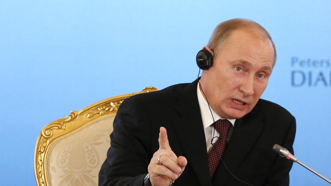 Russian President Vladimir Putin, gestures as he speaks during a Russian-German business forum  in the Grand Kremlin Palace in Moscow, Friday, Nov. 16, 2012. Putin shot back at visiting German Chancellor Angela Merkel for raising questions about the imprisonment of the Pussy Riot punk provocateurs, suggesting she was poorly informed about the group's true nature. (AP Photo/Alexander Zemlianichenko)