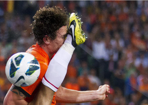 Daryl Janmaat of the Netherlands is kicked by Arda Turan of Turkey during their 2014 World Cup qualifying match in Amsterdam