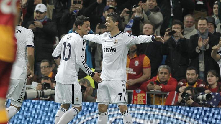 Real Madrid's Cristiano Ronaldo from Portugal, right, celebrates with Mesut Ozil from Germany, left, after scoring against Galatasaray's during the Champions League quarterfinal first leg soccer match between Real Madrid and Galatasaray at the Santiago Bernabeu stadium in Madrid, Wednesday, April 3, 2013. (AP Photo/Andres Kudacki)