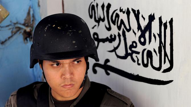 "An Indonesian police officer stands guard at the door of the house of a suspected terrorist after a raid in Jakarta, Indonesia, Saturday, Oct. 27, 2012. Indonesian police say they have arrested 11 people suspected of planning a range of terrorist attacks on domestic and foreign targets including the U.S. and Australian embassies. Arabic writing in the background reads ""There is no God but Allah and Muhammad is His messenger."" (AP Photo/Jefta)"