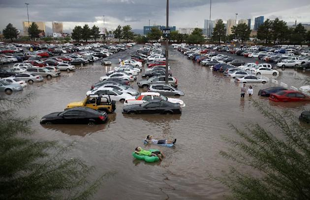 University of Nevada, Las Vegas students Ryan Klorman, top, and Markus Adams, relax on inflatable pool toys in floodwater at UNLV in Las Vegas Tuesday, Sept. 11, 2012. Intense thunderstorms drenched p