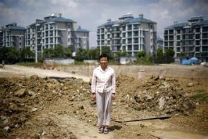 Xu poses at a construction site area where her house stood in Wuxi