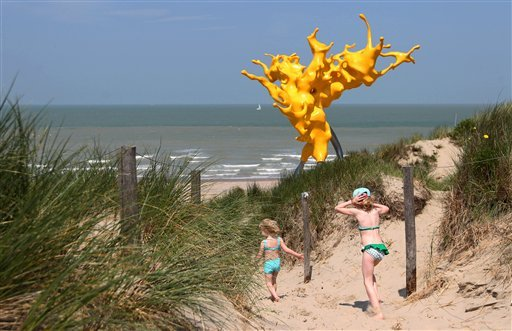 Girls run in front of a sculpture entitled Olnetop, magnified splashing waves, by Belgian artist Nick Ervinck, during the Beaufort04 Triennial of Contemporary Art exhibition along the Belgian coast, i