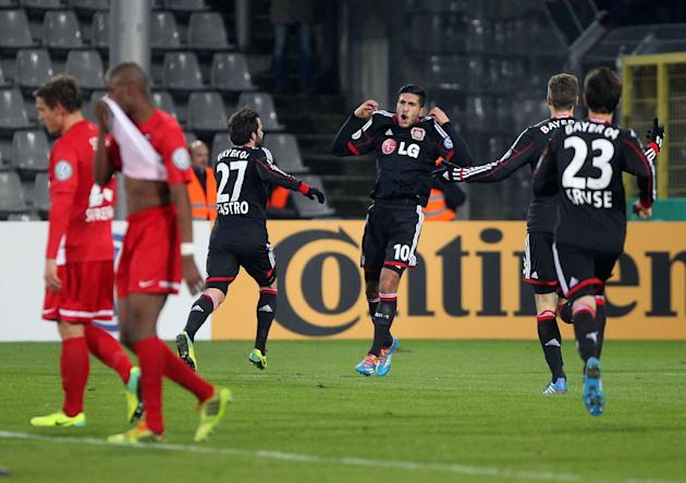 Leverkusen's Emre Can, center, celebrates scoring during a round of 16 German soccer cup match between SC Freiburg and Bayer Leverkusen in Freiburg, Germany, Wednesday Dec. 4, 2013