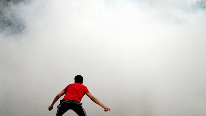 A Bahraini anti-government protester holding stones confronts riot police, unseen behind clouds of tear gas, during clashes outside the home of jailed human rights activist Nabeel Rajab in Bani Jamra, Bahrain, on Saturday, March 23, 2013. Security forces in Bahrain fired tear gas to prevent protesters from reaching the house of Rajab, who is the focus of an international campaign seeking his release.(AP Photo/Hasan Jamali)
